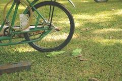 Uitstekende Groene Fiets op Gras met de Aanpassing van Plastic Schoenen stock foto's