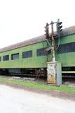 Uitstekende groene spoorwegpersonenauto met gedeeltelijk ingescheepte vensters en het oude licht van het spoorwegspoor Stock Afbeeldingen