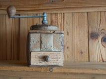 Uitstekende hand cranck koffiemolen, houten raadsachtergrond stock afbeelding