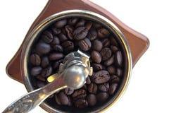Uitstekende handdiekoffiemolen met koffiebonen op witte achtergrond wordt geïsoleerd Stock Fotografie