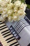 Uitstekende harmonika en een boeket van witte rozen royalty-vrije stock afbeelding