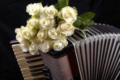 Uitstekende harmonika en een boeket van witte rozen royalty-vrije stock afbeeldingen