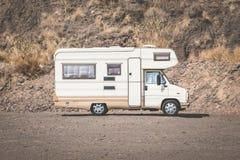 Uitstekende het kamperen bus, rv-kampeerauto in woestijnlandschap, royalty-vrije stock afbeelding