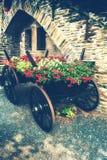 Uitstekende houten die wain met bloeiende rode geranium wordt verfraaid Stock Afbeelding