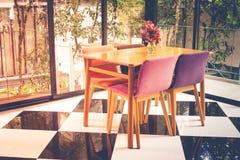 Uitstekende houten lijst en stoel op geruite patroonvloer in woonkamer stock afbeelding