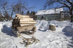 Uitstekende houten slee met brandhouttribunes op een snow-covered pa stock foto's