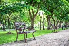 Uitstekende ijzerzetel op voetpad binnen groen park royalty-vrije stock foto