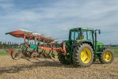 Uitstekende John Deere-tractor die een ploeg trekken Royalty-vrije Stock Foto's