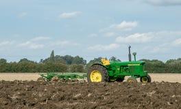 Uitstekende John Deere-tractor die een ploeg trekken Royalty-vrije Stock Foto