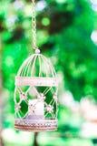 Uitstekende kaars in decoratieve vogelkooi Witte birdcage op bloemenachtergrond Huwelijksdecoratie, groene gebladerte en lantaarn stock foto's