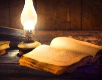 Uitstekende kerosinelantaarn en open oud boek stock afbeeldingen