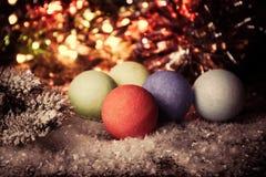 Uitstekende Kerstmis, Nieuwjaarachtergrond met veelkleurige Kerstmisdecoratie op sneeuw Stock Foto's
