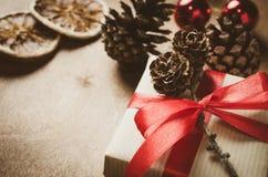Uitstekende Kerstmisachtergrond Kraftpapier-dozen met giften, met rode linten en denneappels in rustieke stijl worden gebonden di royalty-vrije stock foto