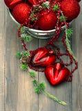 Uitstekende Kerstmisachtergrond met rode snuisterijen en harten Royalty-vrije Stock Afbeeldingen