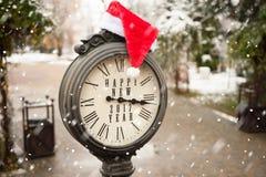 Uitstekende klok met santahoed en woorden Gelukkig Nieuwjaar Stock Afbeeldingen