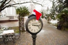 Uitstekende klok met santahoed en woorden Vrolijke Kerstmis Stock Foto's