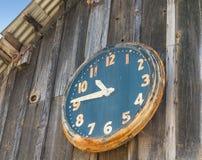 Uitstekende klok op een schuurmuur Stock Fotografie