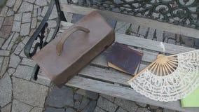 Uitstekende koffer, boeken en een ventilator op de bank stock videobeelden