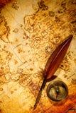 Uitstekende kompas en gansganzepen die op een oude kaart liggen. stock foto