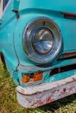 Uitstekende koplamp in een oude, verlaten blauwe bestelwagen met een roestige bumper royalty-vrije stock foto's