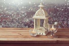 Uitstekende lantaarn met kaarsen over de achtergrond van de de winterstad met exemplaarruimte Stock Foto's