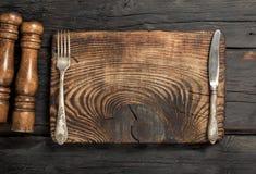 Uitstekende lege raad met vork en mes op houten lijst Royalty-vrije Stock Afbeeldingen
