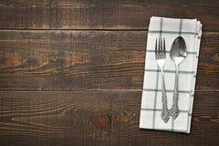 Uitstekende lepels en vork met napery op houten achtergrond Royalty-vrije Stock Afbeelding