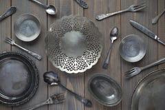 Uitstekende lepels, vorken, messen en metaalplaten op een grijze houten achtergrond royalty-vrije stock fotografie