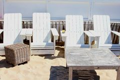 Uitstekende ligstoelen en rieten lijst bij het strand Stock Foto's