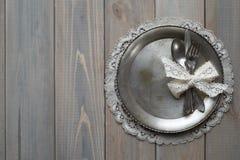 Uitstekende mes, lepel en vork op een metaalplaat op een grijze houten achtergrond royalty-vrije stock foto's