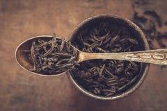 Uitstekende metaalkop van droge theebladen en lepel Royalty-vrije Stock Afbeelding
