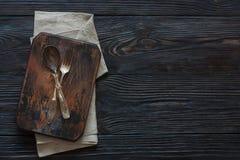 Uitstekende metaallepel en vork op een houten donkere achtergrond Stock Foto