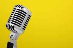 Uitstekende microfoon die op geel wordt geïsoleerdt Stock Foto's