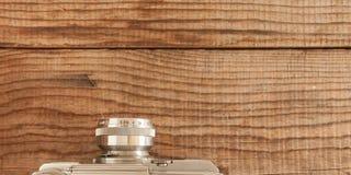 Uitstekende 35mm filmen camera met gebouwd in meter, die over een gedateerde houten achtergrond liggen Stock Afbeelding