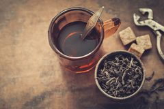 Uitstekende mok van zwarte of aftreksel, rustieke metaalkop droge theebladen, suikerkubussen en suikertang Royalty-vrije Stock Foto