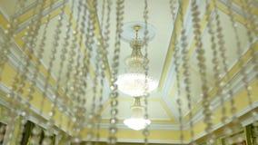Uitstekende mooie kristalkroonluchters op het plafond, grote plechtige zaal stock videobeelden