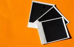 Uitstekende onmiddellijke foto's op oranje achtergrond Royalty-vrije Stock Foto's