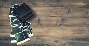 Uitstekende onmiddellijke fotokaders en camera op rustieke houten backgro Stock Fotografie