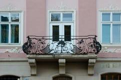 Uitstekende open smeedijzerbalkons op de achtergrond van vensters en roze muur Royalty-vrije Stock Afbeeldingen
