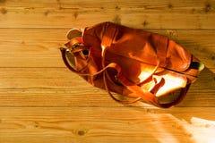 Uitstekende oranje unisex-leerzak op de houten vloer Royalty-vrije Stock Afbeeldingen