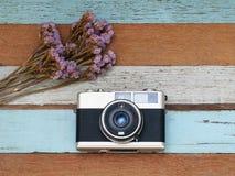 Uitstekende oude camera met bloem op oude houten Stock Foto's