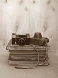 Uitstekende oude film foto-camera met leergeval op houten achtergrond, sepia Stock Afbeelding
