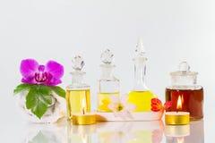 Uitstekende oude flessen aromatische oliën met kaarsen, bloemen, groen blad en witte handdoek op glanzende witte lijst aangaande  Stock Afbeeldingen
