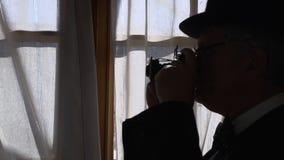 Uitstekende oude mens die door een oude camera FDV schieten stock videobeelden