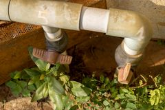 Uitstekende Oude Plastic Watertapkraan met pvc-Klep - Verlaten Tuin met Groene Zonnige Installaties - royalty-vrije stock afbeelding