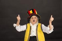 Uitstekende oude vrouw die cilinder en een geel vest dragen royalty-vrije stock fotografie