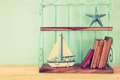 Uitstekende plank met boot, oude boeken en zeester royalty-vrije stock fotografie