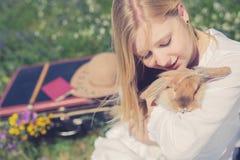 Uitstekende portretfoto van tienermeisje met konijntje in de aard Stock Foto