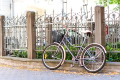 Uitstekende retro fiets dichtbij de omheining van het metaalijzer outdoors stock afbeeldingen