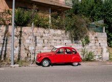 Uitstekende rode auto op de straat in het zuiden van Europa dichtbij het overzees stock fotografie